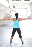 Back view of sporty woman holding pink barbell with both arms stretched out. For shoulder strengthening, outdoors royalty free stock images
