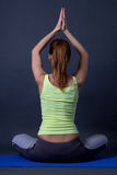Back view of sporty woman sitting in lotus position over grey Stock Images