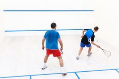Squash players back view. Back view of squash players hitting a ball in a squash court. Squash players in action. Men playing match of squash. Sports, people Royalty Free Stock Photo