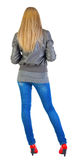 Back view of standing beautiful blonde Young woman. royalty free stock image