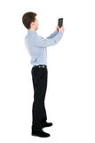 Back view of standing business man photographing a phone or tabl Royalty Free Stock Photography