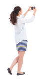 Back view of standing curly woman with mobile phone in the hands Royalty Free Stock Images