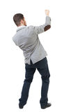 Back view of standing man pulling a rope from the top or cling t Stock Photography