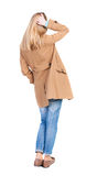 Back view of standing young beautiful  blonde woman in brown clo Stock Image