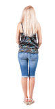Back view of standing young beautiful blonde woman. She shyly looks at something. girl watching. Rear view people collection. backside view of person. Isolated royalty free stock image