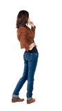 Back view of standing young beautiful  brunette woman in brown j. Acket. girl  watching. Rear view people collection.  backside view of person.  Isolated over Royalty Free Stock Photography