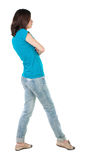 Back view of standing young beautiful  brunette woman in jeans. Stock Image
