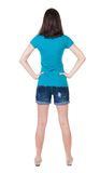 Back view of standing young beautiful  brunette woman in shorts. Stock Photography