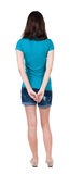 Back view of standing young beautiful  brunette woman in shorts. Royalty Free Stock Photos
