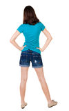 Back view of standing young beautiful  brunette woman in shorts. Royalty Free Stock Image