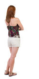 Back view of standing young beautiful  brunette woman in shorts. Stock Images