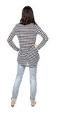Back view of standing young beautiful  brunette woman in striped Stock Photo