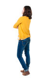 Back view of standing young beautiful  brunette woman in yellow Royalty Free Stock Image