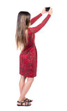 Back view of standing young beautiful  girl with mobile phone in Royalty Free Stock Photos