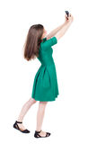 Back view of standing young beautiful  girl with mobile phone in Stock Photography