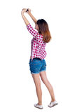 Back view of standing young beautiful  girl with tablet computer in the hands of Stock Photo