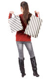 Back view of standing young beautiful  woman. Back view of going  woman  in  sweater woman with shopping bags . beautiful brunette girl in motion.  backside Stock Images