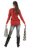 Back view of standing young beautiful  woman. Back view of going  woman  in  sweater woman with shopping bags . beautiful brunette girl in motion.  very Royalty Free Stock Photo