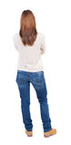 Back view of standing young beautiful  woman in jeans. Royalty Free Stock Photos