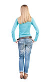 Back view of standing young beautiful  woman in jeans. Royalty Free Stock Photography