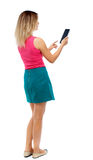Back view of standing young beautiful  woman using a mobile phon Royalty Free Stock Image
