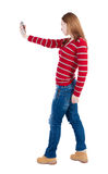 Back view of standing young beautiful  woman and using a mobile Royalty Free Stock Image