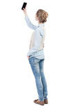 Back view of standing young beautiful  woman using a mobile Stock Photography