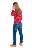 Back view of standing young beautiful  woman and using a mobile Royalty Free Stock Photography