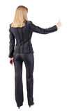 Back view of standing young blonde business woman showing thumb. Up. beautiful businesswoman in black suit gesturing ok sign. Rear view people collection Stock Images