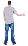 Back view of standing Young brunette man showing thumb up. Stock Photo