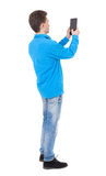 Back view of standing young man with tablet computer in the hand Stock Images
