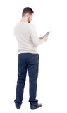 Back view of standing young man with tablet computer in the hand Royalty Free Stock Photography