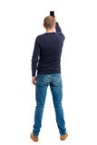 Back view of standing young man and using a mobile phone. Royalty Free Stock Photography