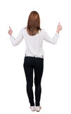 Back view of standing young redhead business woman showing thumb Stock Photos