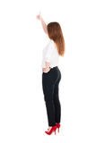 Back view of standing young redhead business woman showing thumb. Up. beautiful businesswoman in black suit gesturing ok sign. Rear view people collection Royalty Free Stock Photo