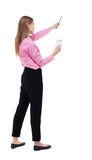 Back view of  stands woman takes notes in a notebook. girl  watc Royalty Free Stock Images