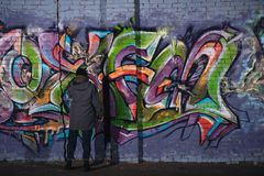 back view of street artist painting colorful graffiti on wall stock photo