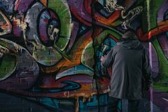 back view of street artist painting graffiti with aerosol paint on wall royalty free stock photos