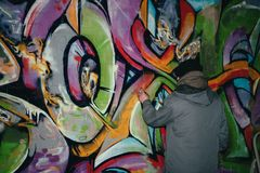 back view of street artist painting graffiti with aerosol paint on wall royalty free stock photo
