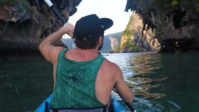 Back View of Strong Man on Kayak in the Open Sea Water. Sunset over the Rock Cliffs. Railey Beach, Krabi, Thailand. stock video