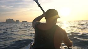 Back view of strong man on kayak in the open sea water. Sunset over the Rock Cliffs. Railey Beach, Krabi, Thailand. stock video footage
