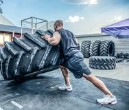 Back view of strong muscular fitness man moving large tire in street gym. Concept lifting, workout training stock photography