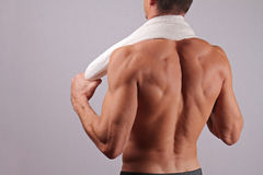 Back view of strong muscular male body, closeup of fitness man with a white towel slung around his neck. bodybuilding, work out, s Stock Photos