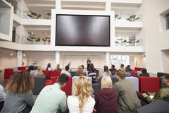Back view of students at a lecture in a university atrium stock photo