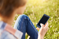Back view of stylish boy holding cell phone with blank sreen downloading video or pictures using free internet sitting on meadow. Stock Images
