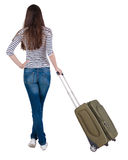 Back view of stylishly dressed brunette woman  with  suitcase lo Royalty Free Stock Photography