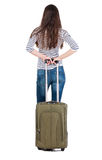 Back view of stylishly dressed brunette woman  with  suitcase lo. Oking up.   Standing young girl . Rear view people collection.  backside view of person Stock Images