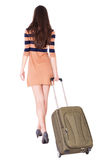 Back view of stylishly dressed brunette woman. With  suitcase looking up.   Standing young girl . Rear view people collection.  backside view of person Royalty Free Stock Photography