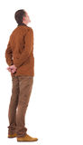 Back view stylishly dressed man in a brown jacket  looking up. Back view of stylishly dressed man in a brown jackett  looking up.   Standing young guy in jeans Royalty Free Stock Image