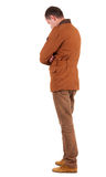 Back view of stylishly dressed man in a brown jackett  looking u. P.   Standing young guy in jeans and  jacket. Rear view people collection.  backside view of Stock Image
